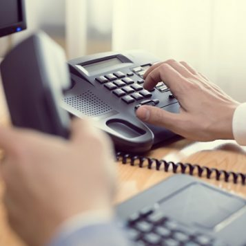 Hand dials a desk phone