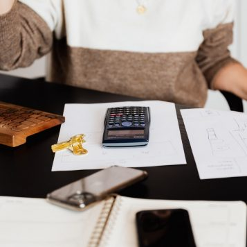 Woman sits at desk with calculator and paperwork