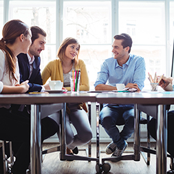 People sit and talk around a conference table