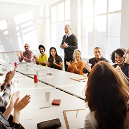 Smiling people sit and clap around a conference table