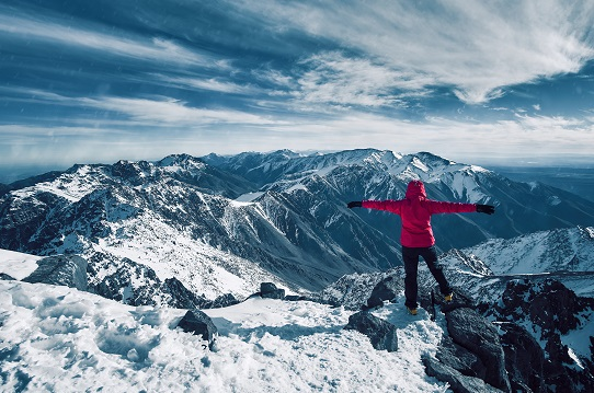 A person in a red parka stands on a mountaintop with arms outstretched