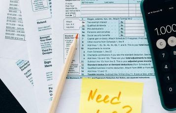 """Stick note labeled """"Need help?"""" on top of tax forms"""