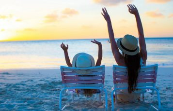 Mother and daughter sit in chairs beside the beach and throw their arms in the air