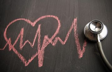 Chalk drawing of a heart and heartbeat beneath a stethoscope