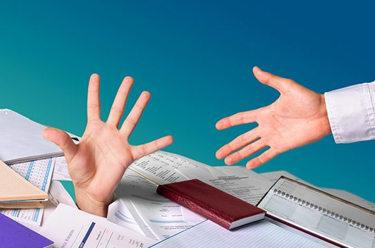 Hand buried under paperwork reaches for help while a hand reaches down to help it