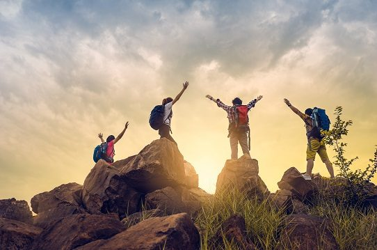 Four climbers with backpacks stand on boulders at the top of a hill with their arms in the air