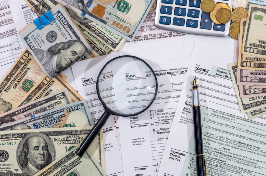 Cash, a calculator, a magnifying glass, and a pen sitting on top of various tax forms