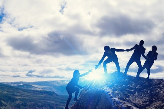 Three people in business attire link hands at the top of a cliff and reach for a fourth woman to pull her up